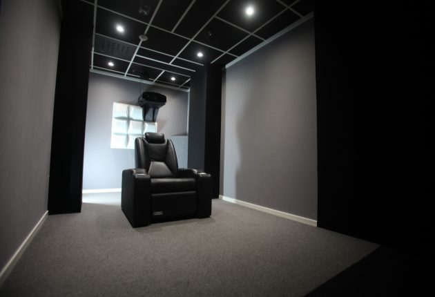 Väggarna är överdragna med grått och svart molton-tyg, som är känt för att ha ljud- och ljusabsorberande egenskaper. På golvet ligger en grå matta och taket har ljudabsorberade plattor av samma typ man brukar hitta på kontor. De mörka och ljusabsorberande materialen minskar reflexer från duken och hjälper till att bevara kontrasten i bilden.